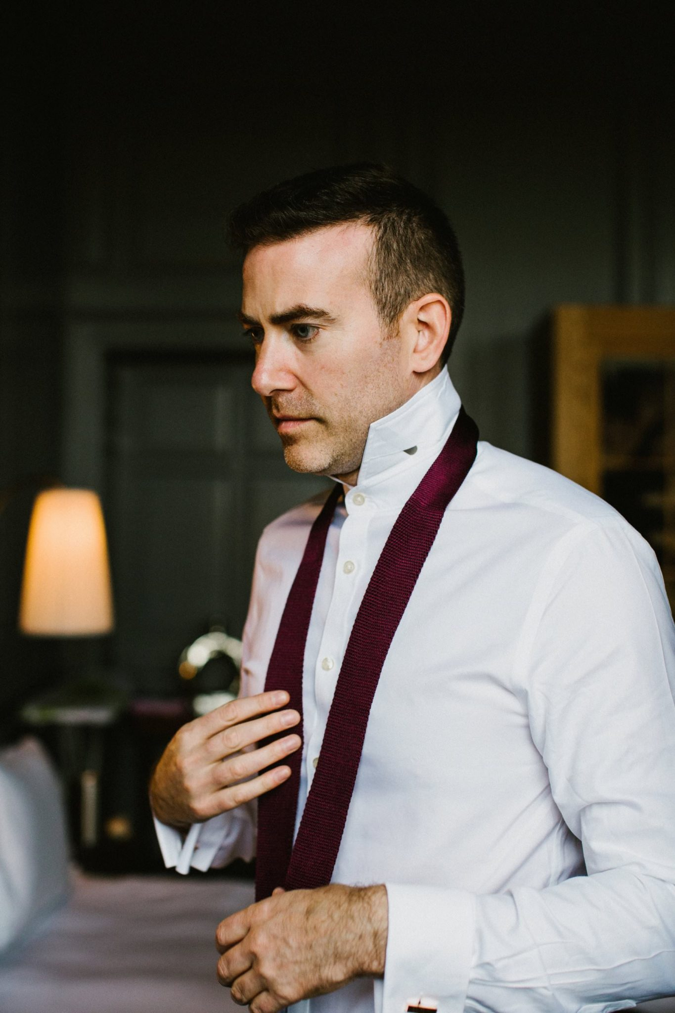 Groom concentrates as he ties his burgundy tie