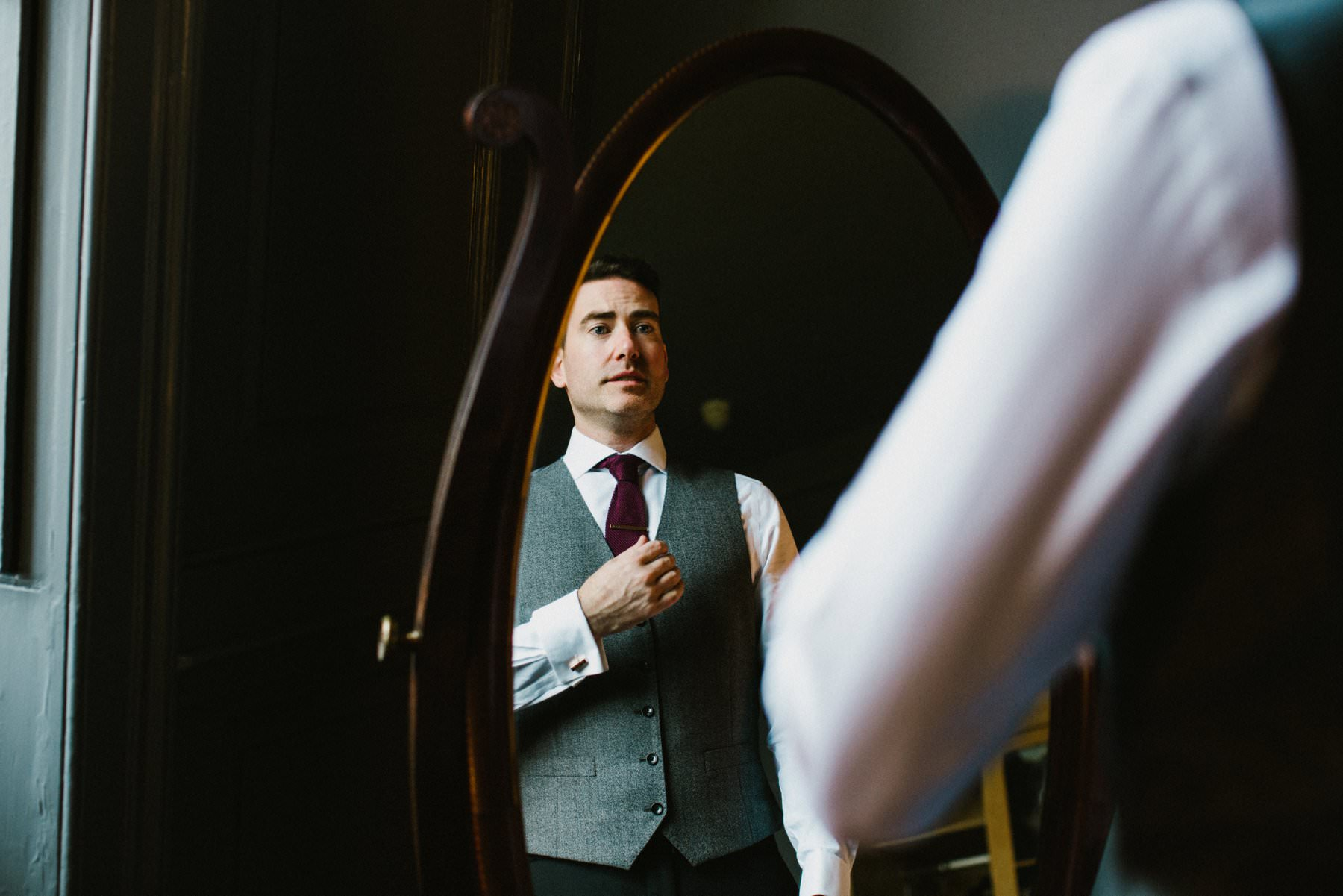 grooms in grey waistcoat and burgundy tie checks himself in the mirror before his wedding at Bellinter House