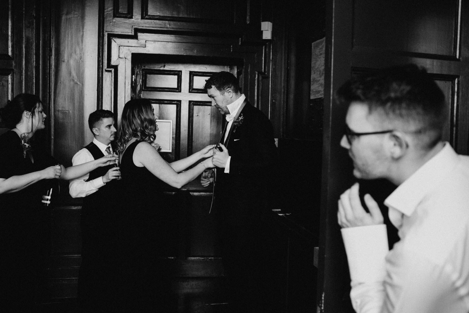 Groom hides from friends in a candid moment of wedding