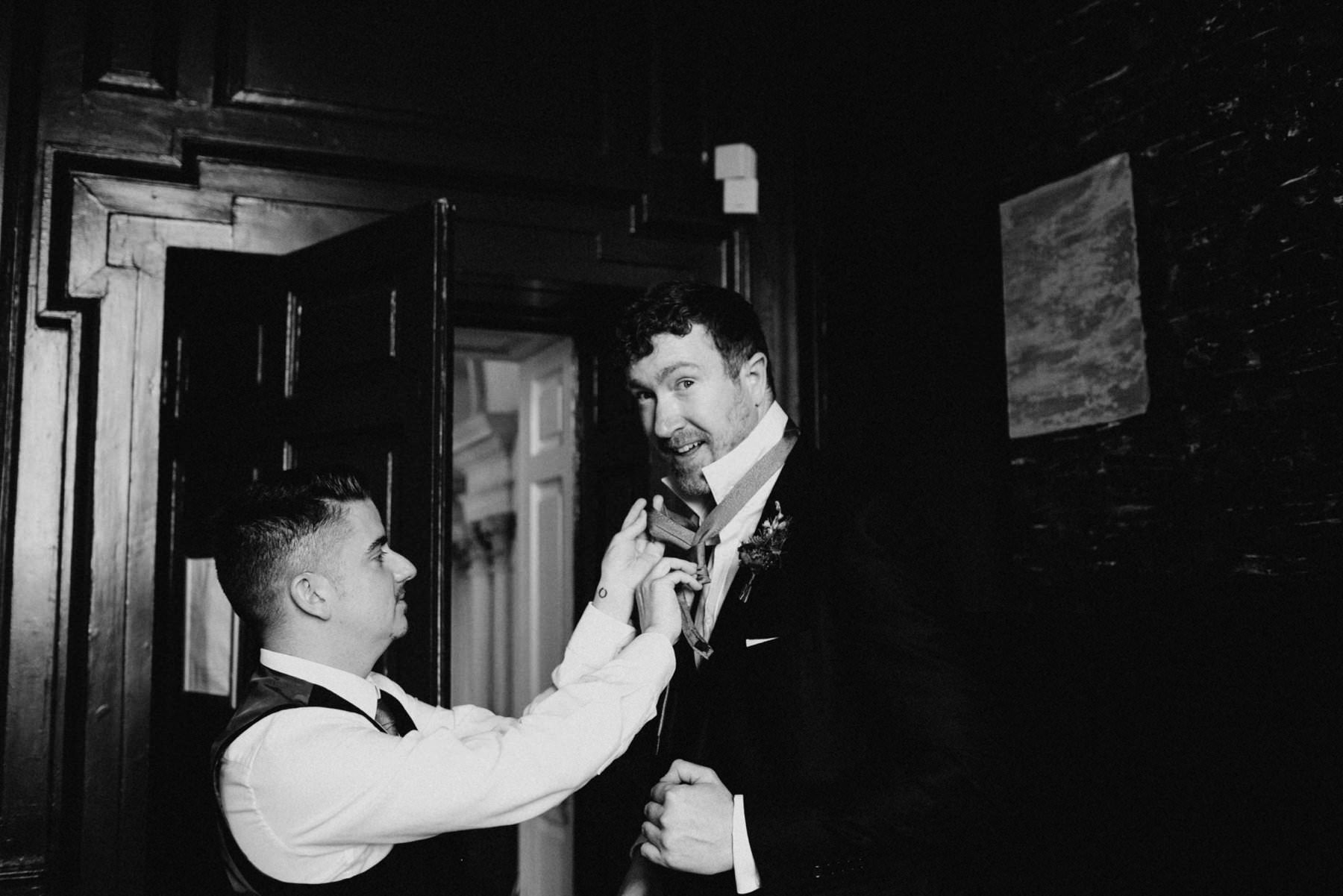 fun moment of groomsmen help each with ties in Bellinter House Navan
