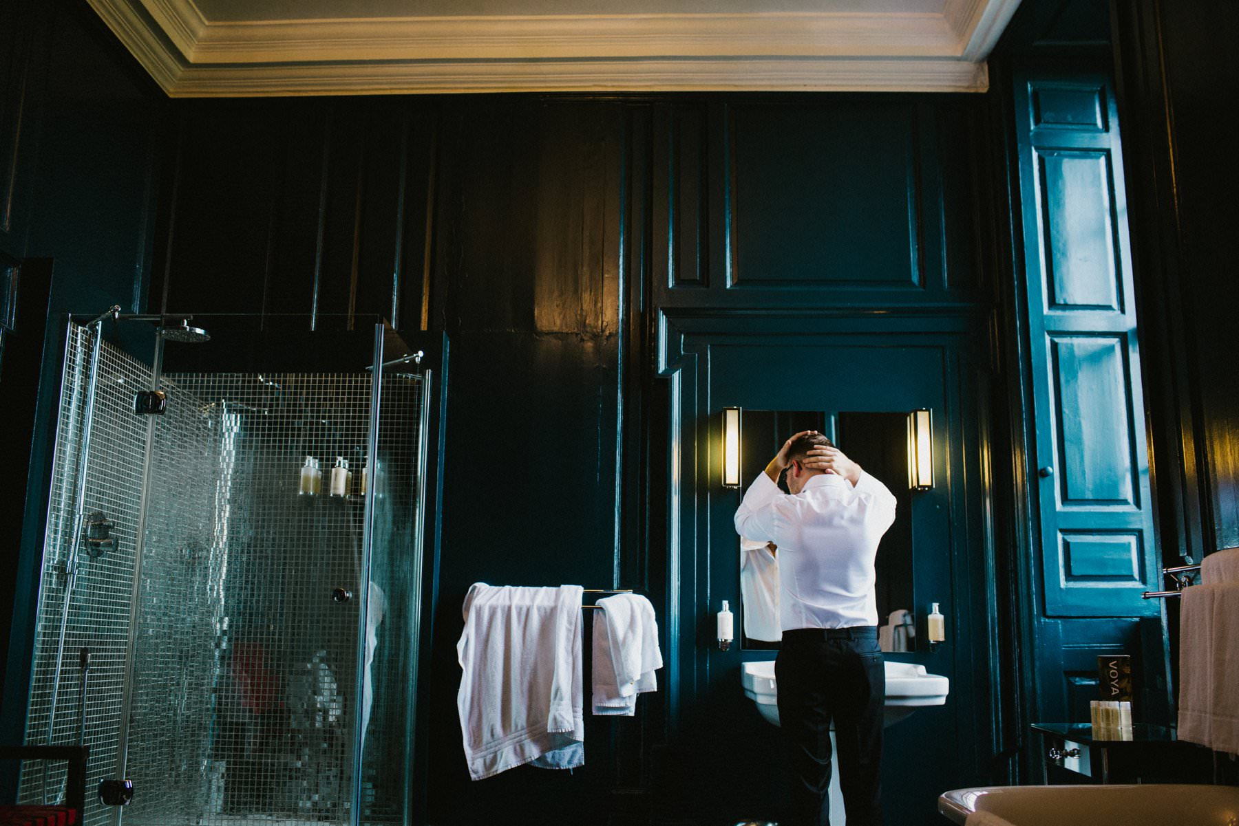 Groom styles hair in blue bathroom of Bellinter House