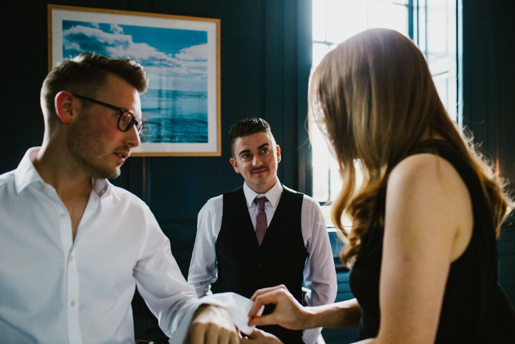 friends help groom get dressed in blue room of bellinter house