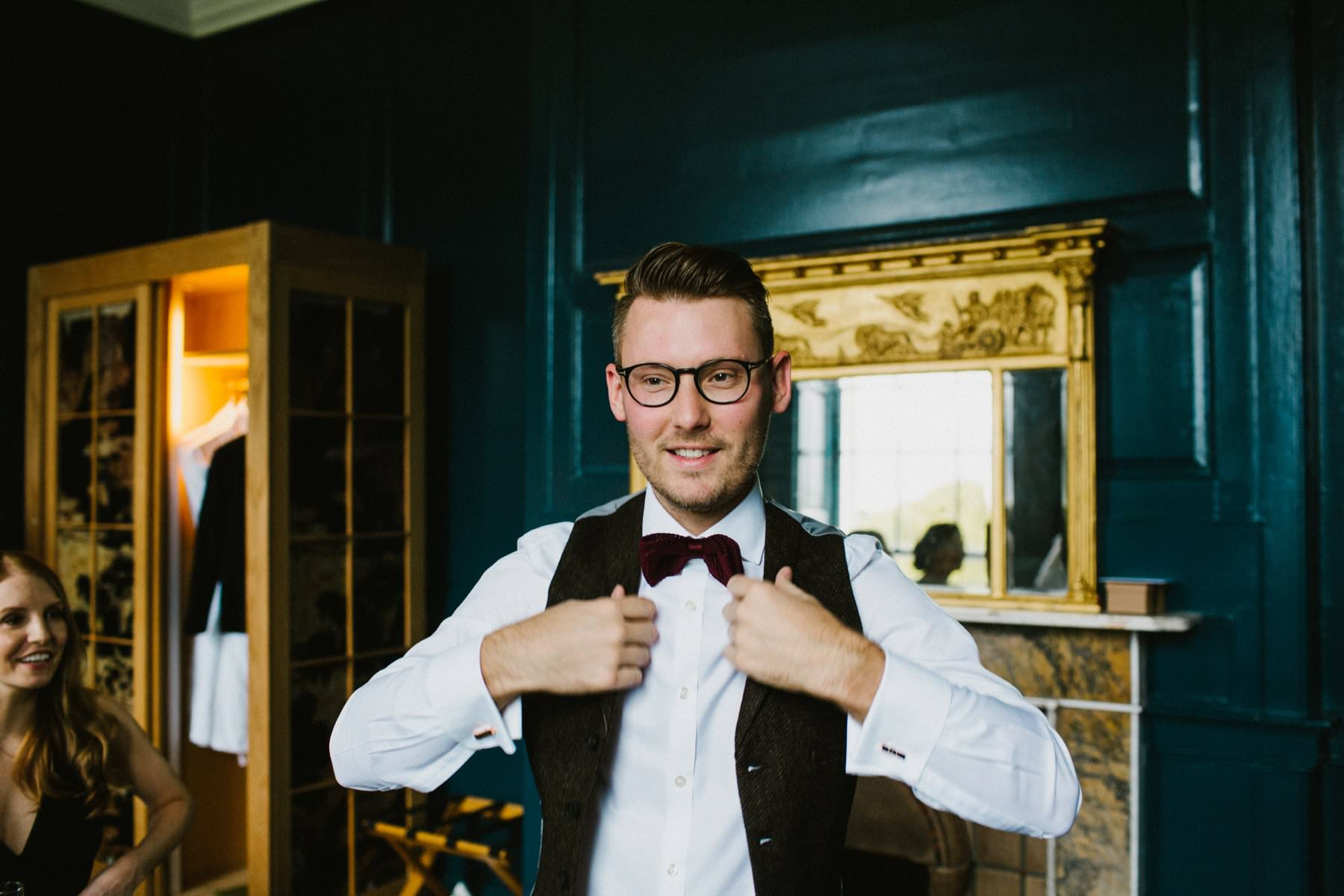 groom wearing glasses and bowtie fixes his waistcoat