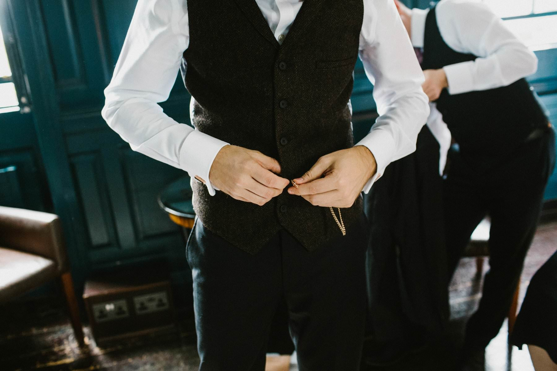 groom buttons last button of dark grey waistcoat