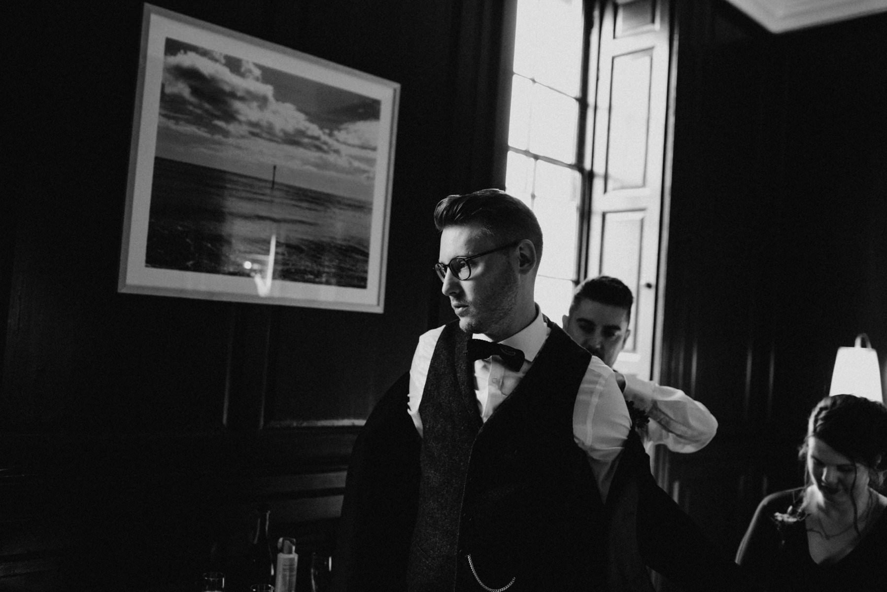 groomsman help groom put on dinner jacket