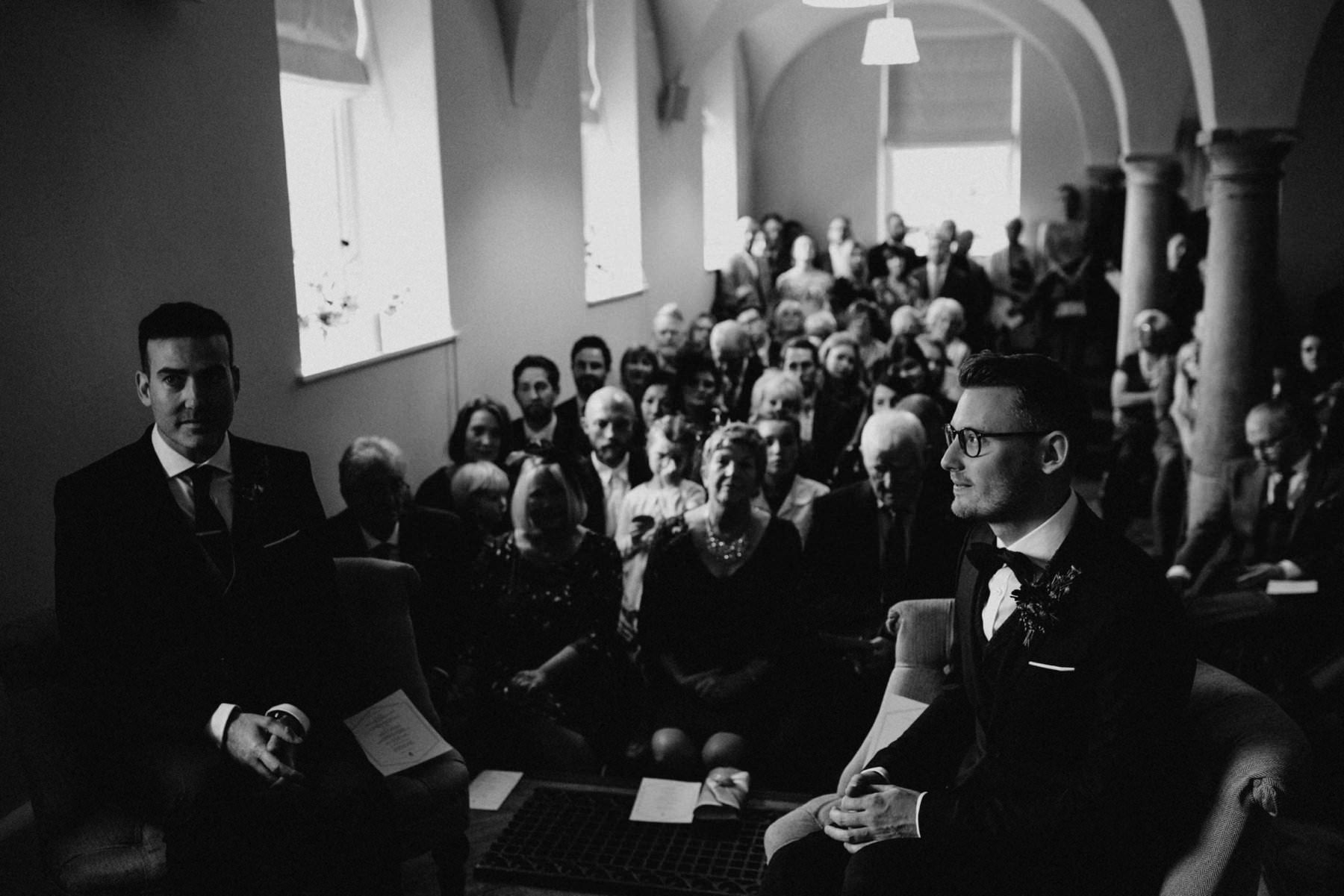 guests watch as two grooms get married in Bellinter House, Ireland