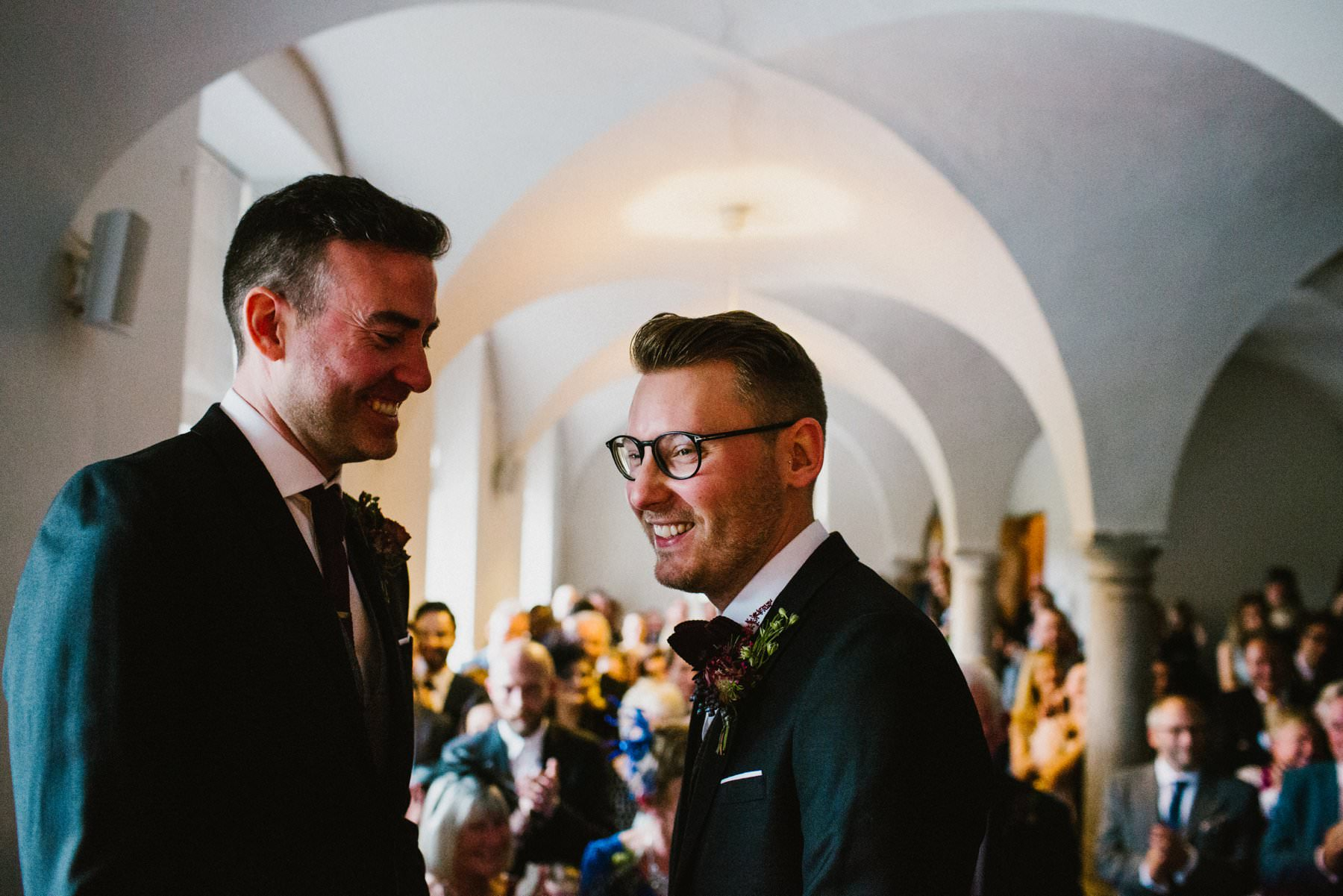 two grooms laugh after their first kiss in bellinter house