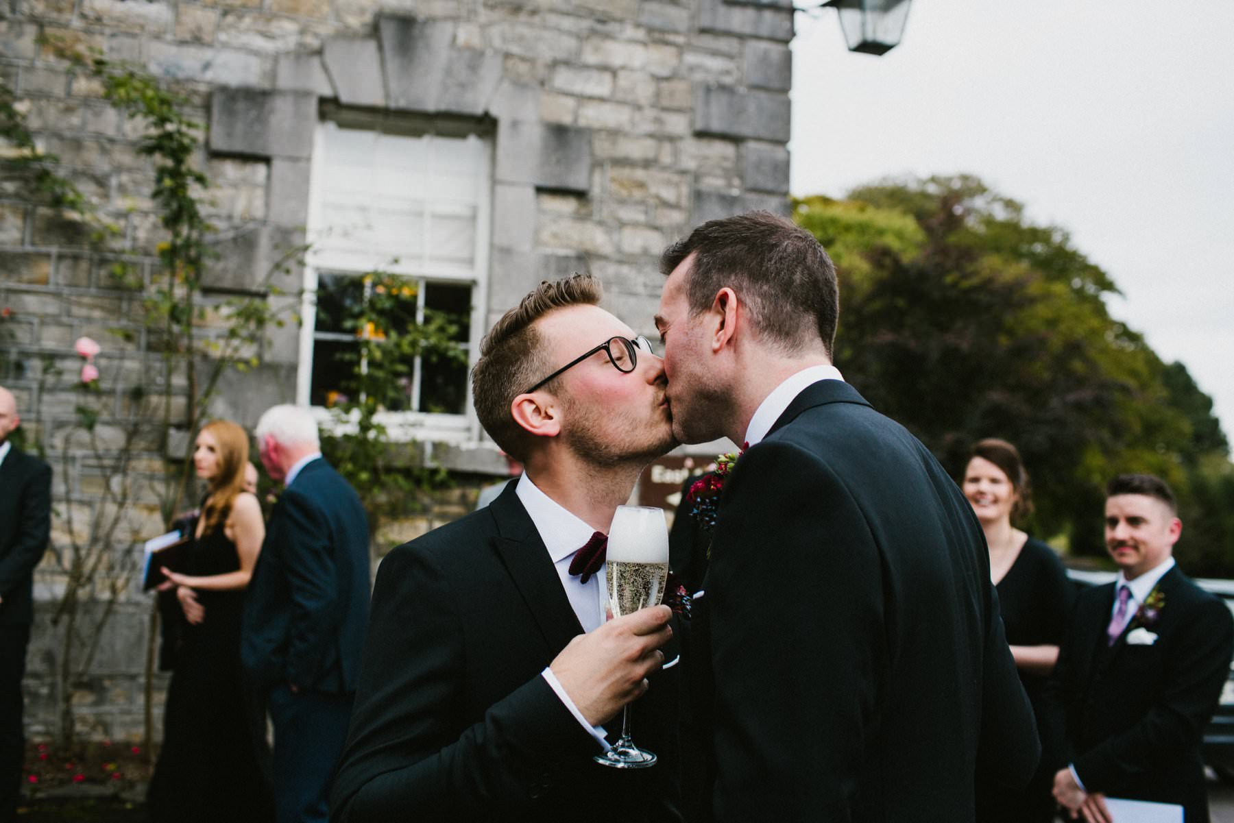 two grooms share kiss and champagne at Bellinter house