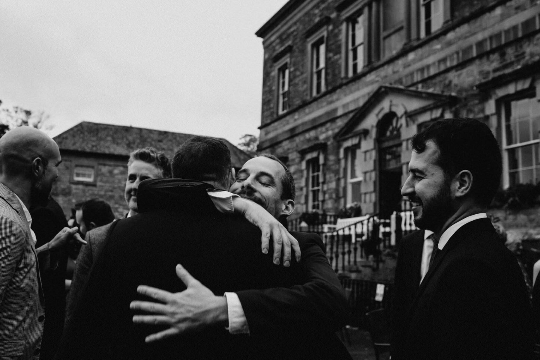 wedding guest hugs groom at irish wedding