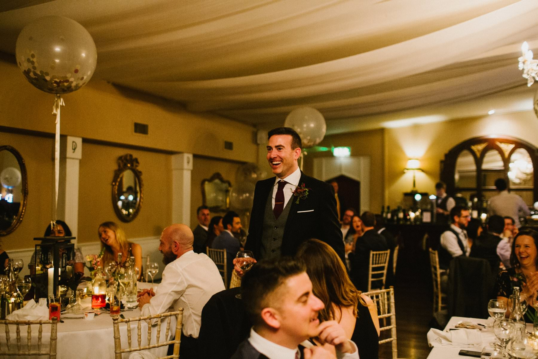 groom laughs in the middle of the reception room in Bellintere House