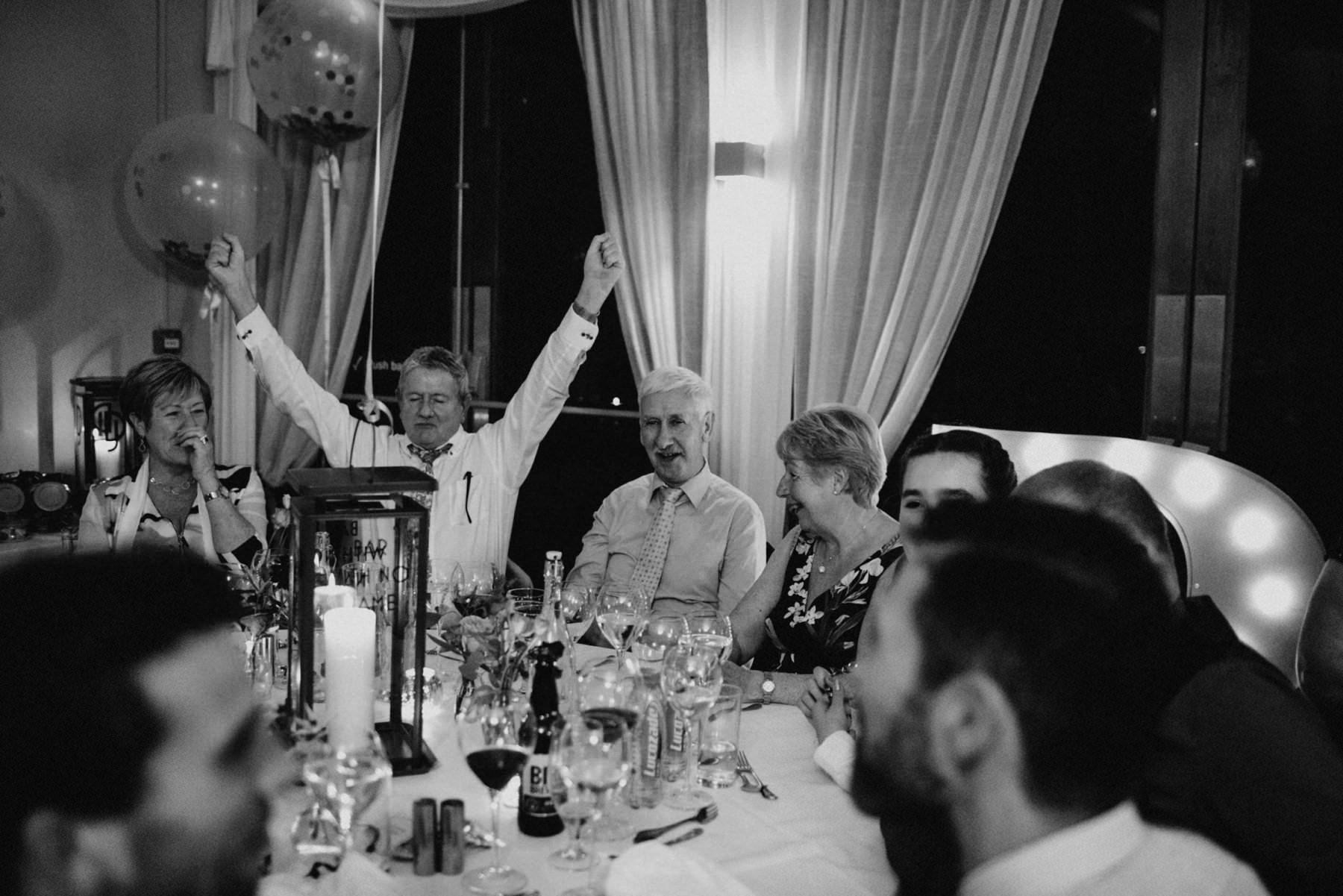 wedding guest cheers during wedding speeches