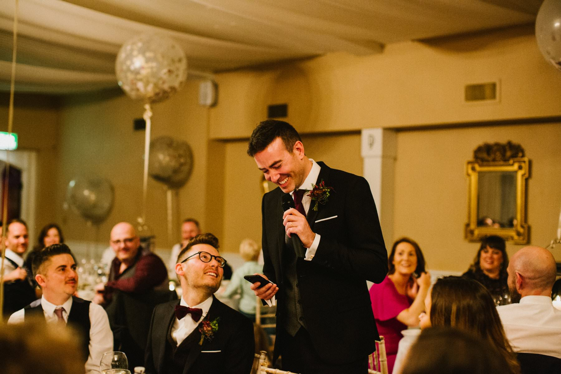 two grooms share moment during wedding speeches