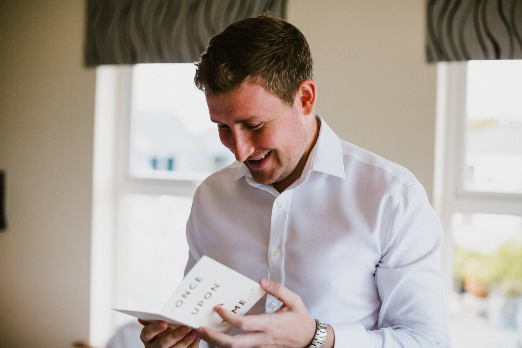 grooms opens card from bride on wedding morning