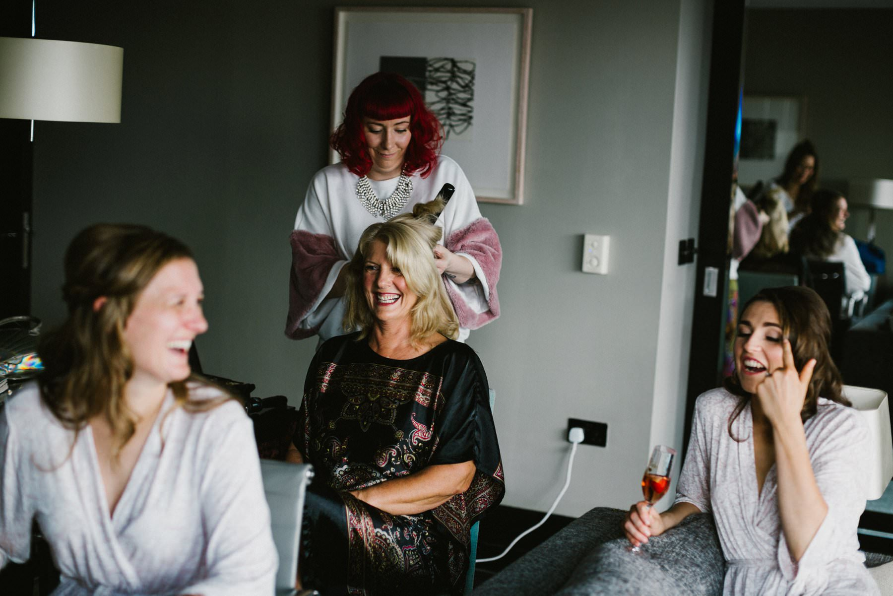 mother of the bride laughing whilst having hair styled