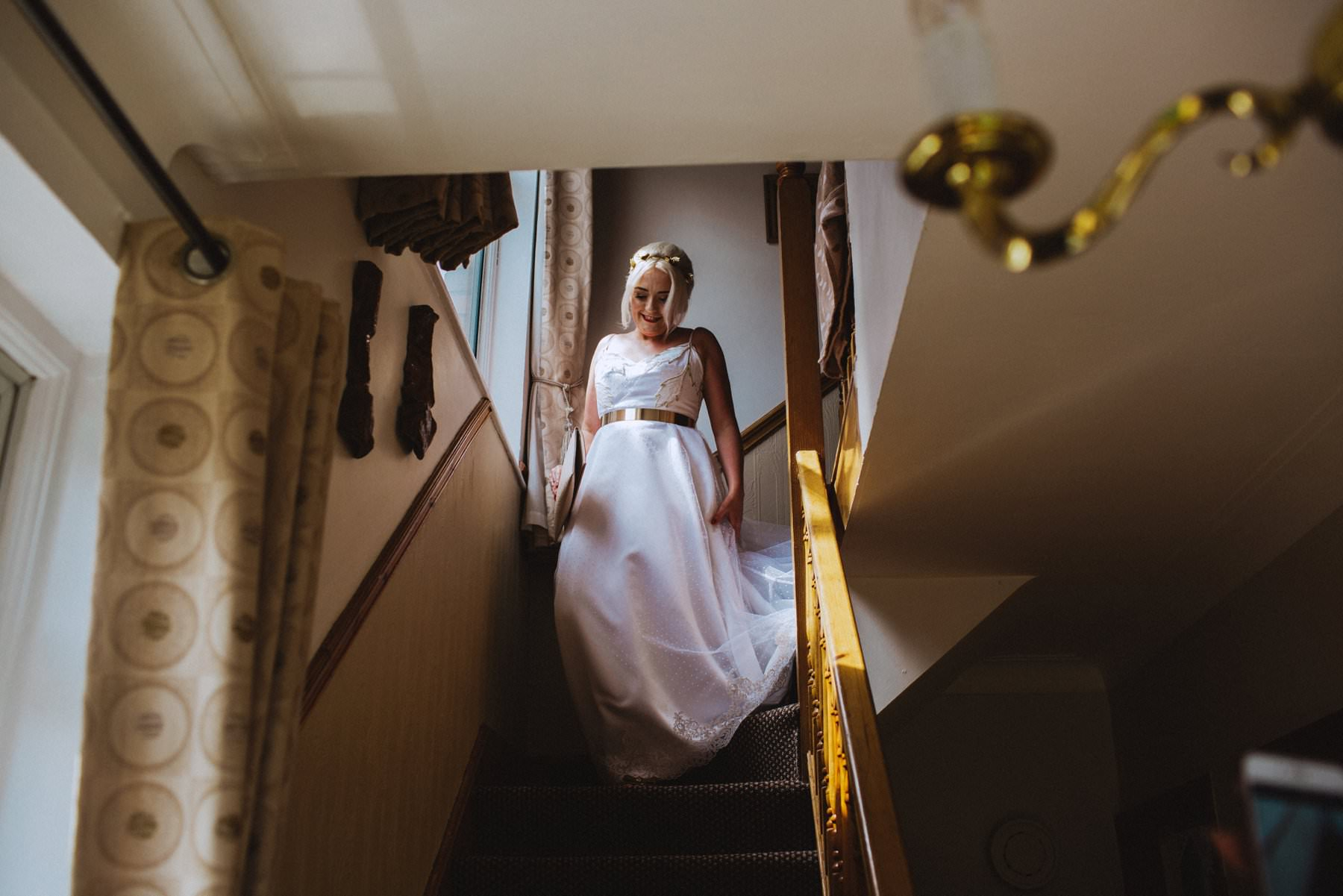 bride walks downstairs for the first time in her wedding dress with a gold band at her waist
