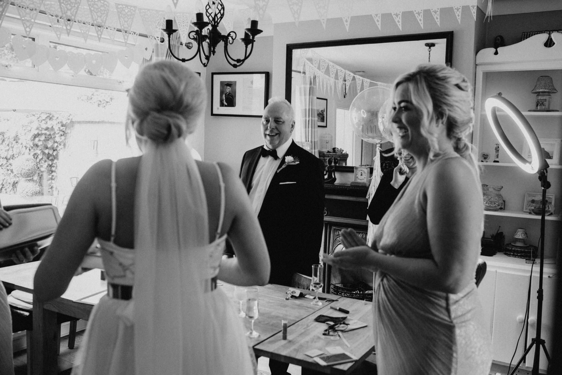 a proud father sees his daughter in her wedding dress for the first time