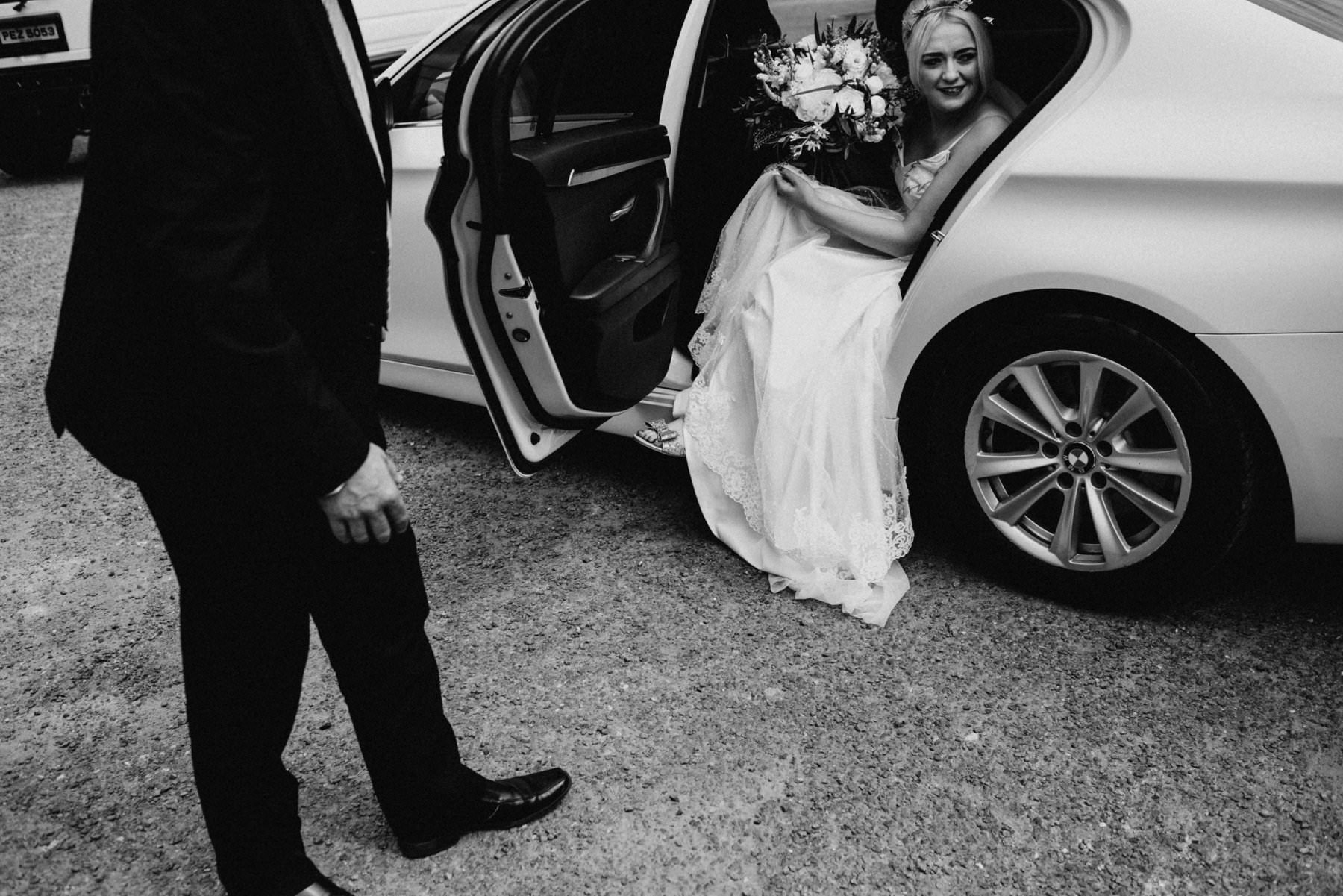 black and white image of a bride arriving to wedding ceremony in a white luxury car