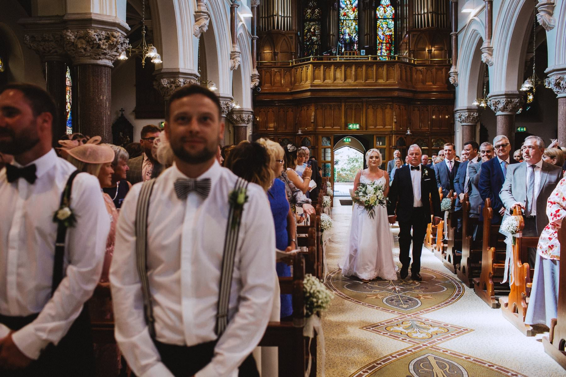 bride is walked down the aisle of a church to her soon to be husband