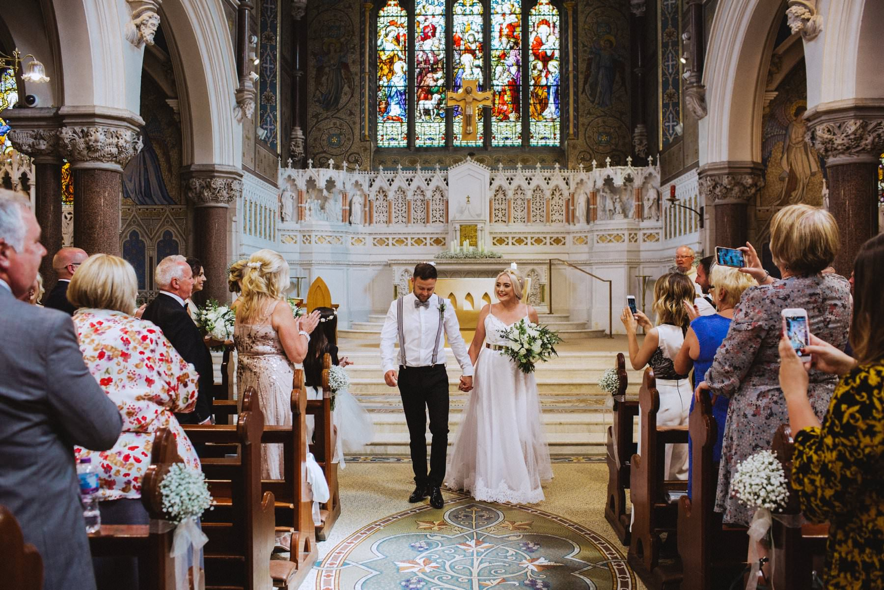 bride and groom walk down the aisle in belfast church