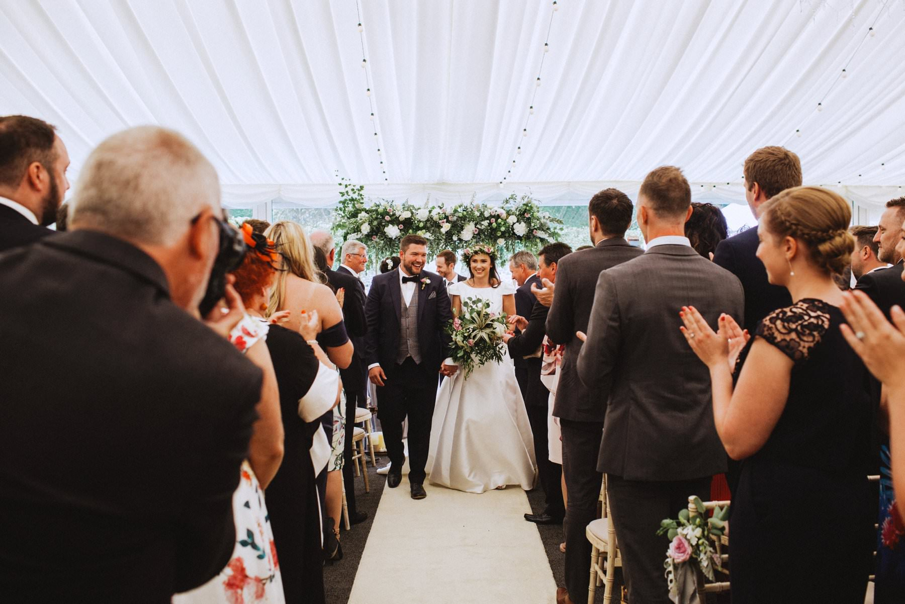 bride and groom walk down ceremony aisle at ivory pavilion northern ireland