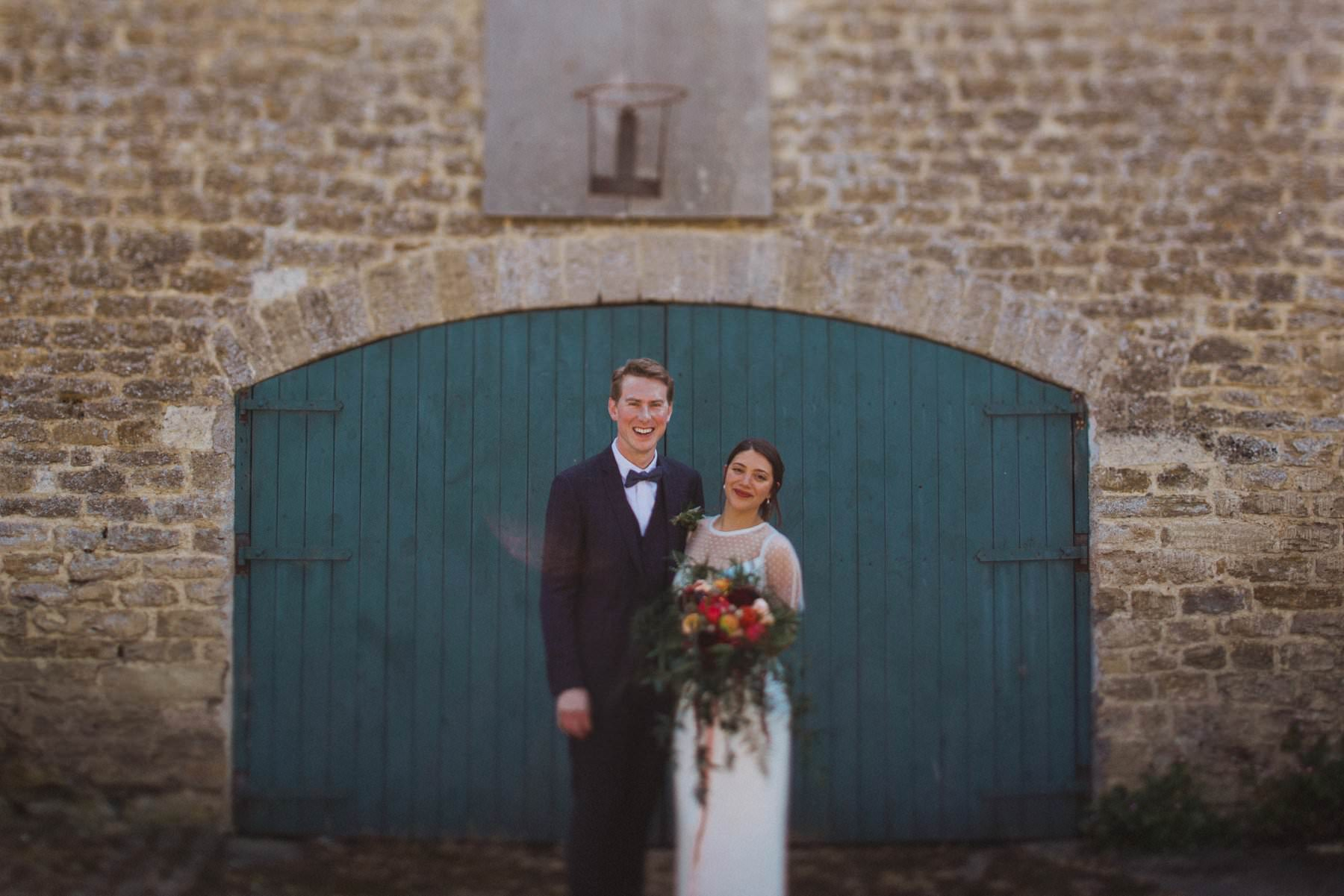 bride and groom pose for wedding portraits in front of barn door at stowford manor farm outside bath