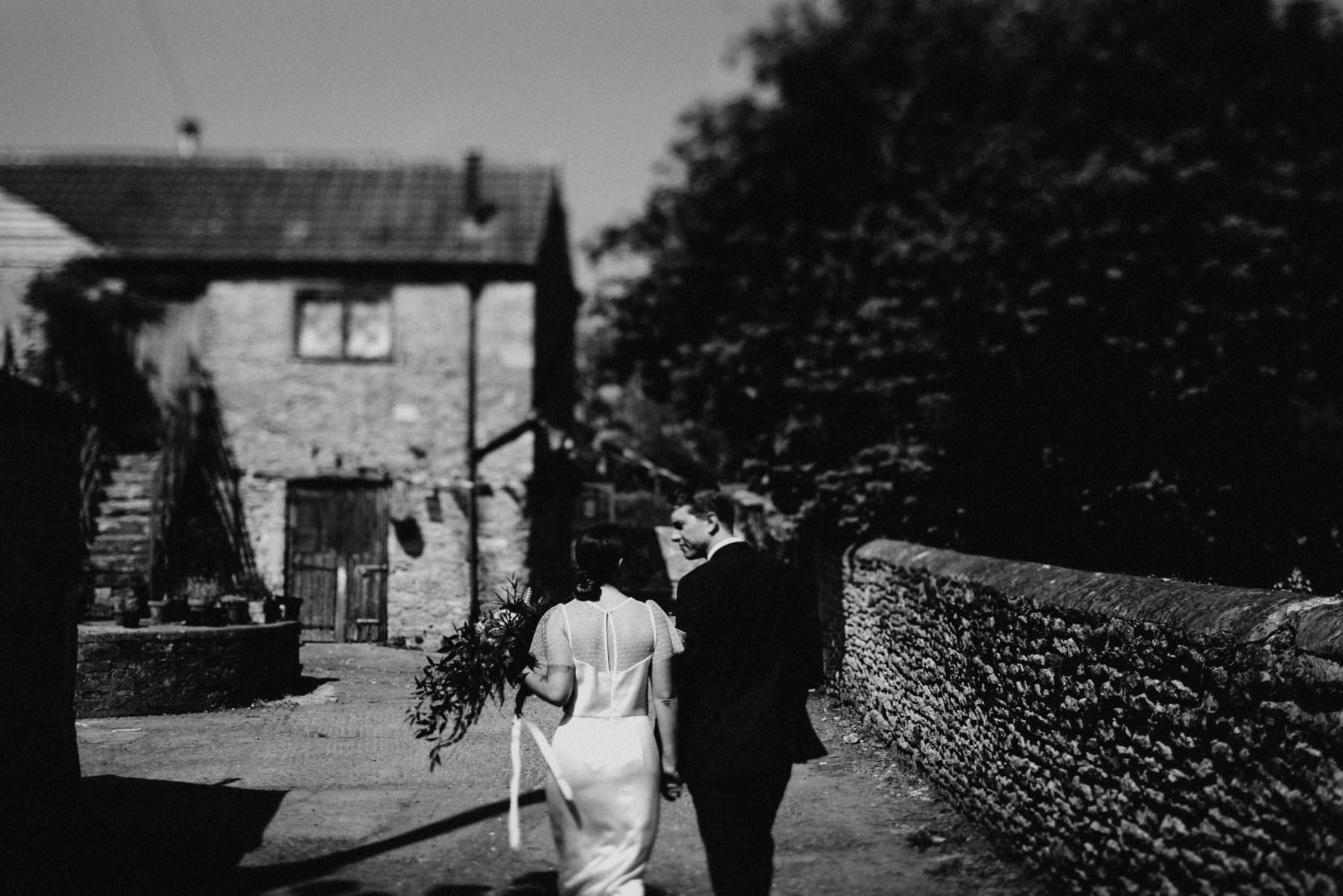 black and white photograph of bride and groom walking through an english farm yard in somerset england