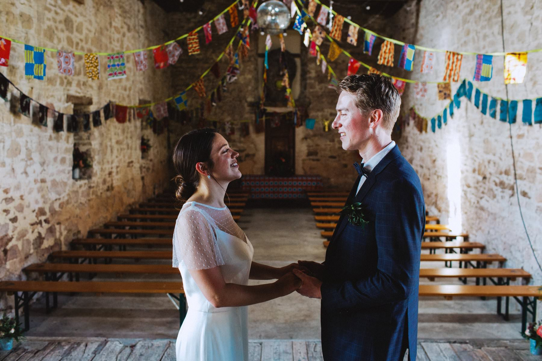 bride and groom stand in the middle of barn wedding ceremony in england