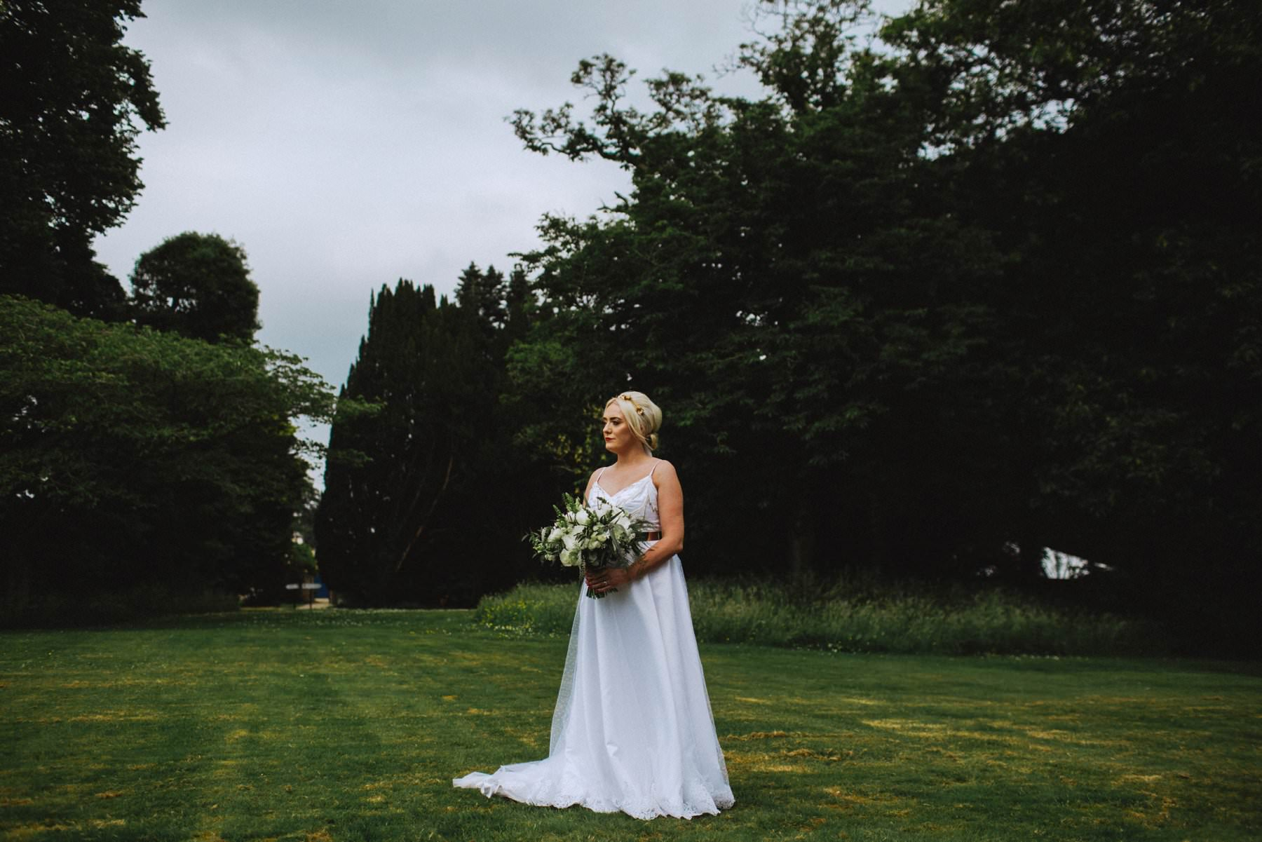 bride stands on the lawn of drenagh house estate limavady