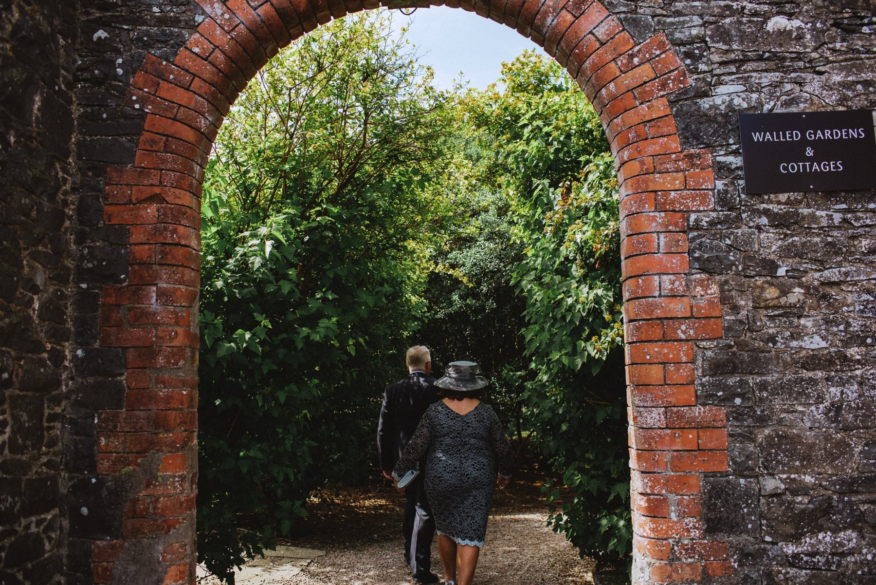 a man a woman both wedding guests walked to the gardens of larchfield estate