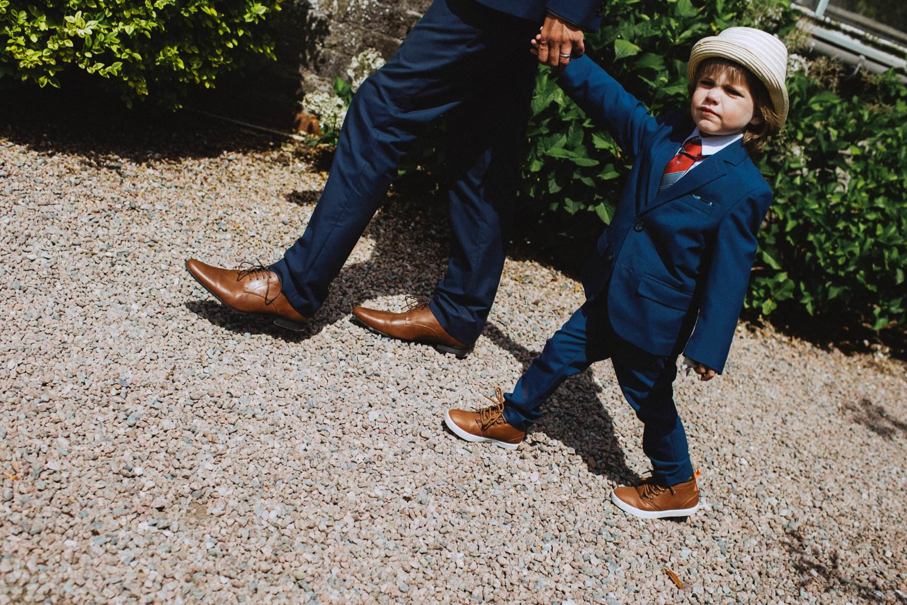 little boy in blue suits and hat holding his parents hand