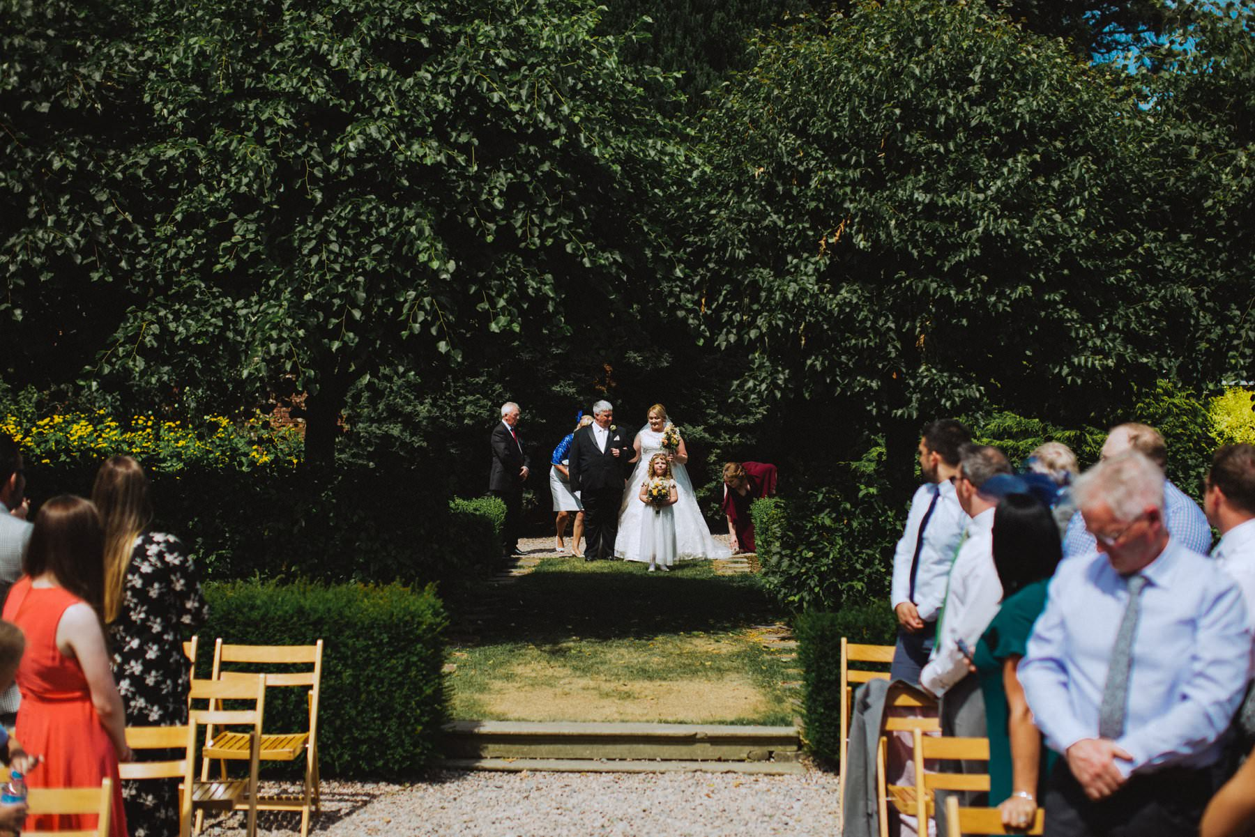 plus size bride walking down the aisle of an outdoor ceremony