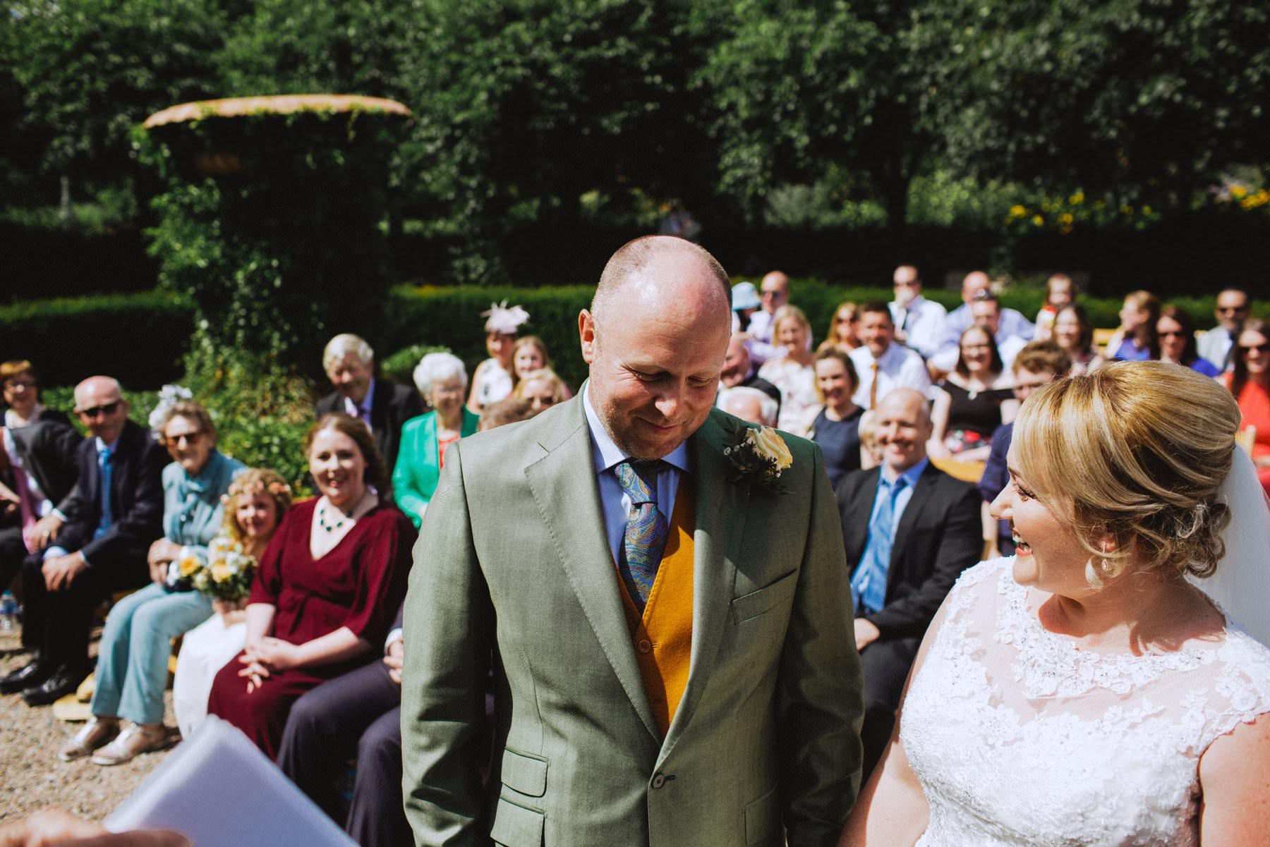 bald groom in green sports jacket gets emotional seeing his bride