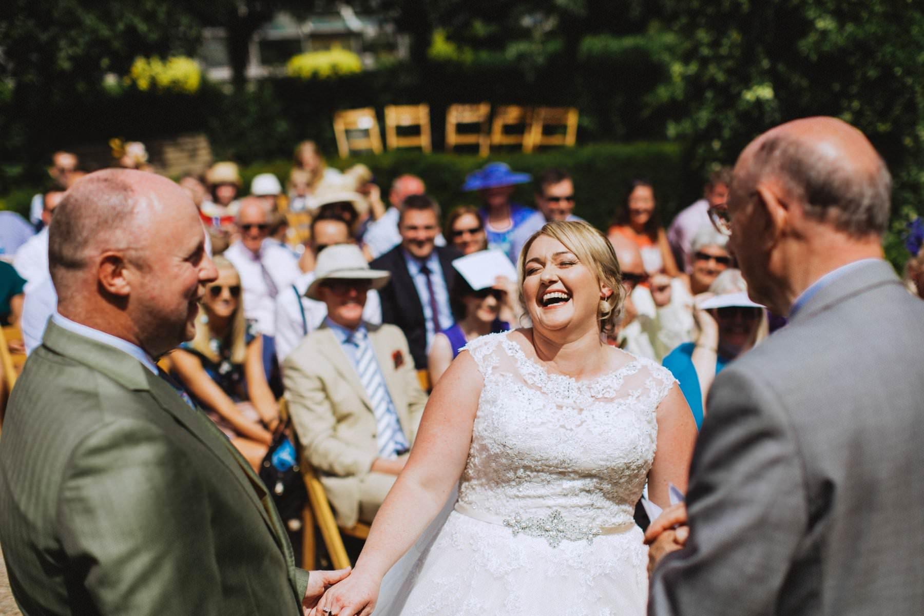 plus size bride laughs during wedding ceremony at larchfield estate