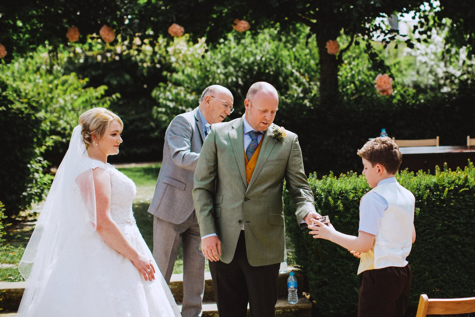 page boy hands over wedding rings at an northern irish wedding