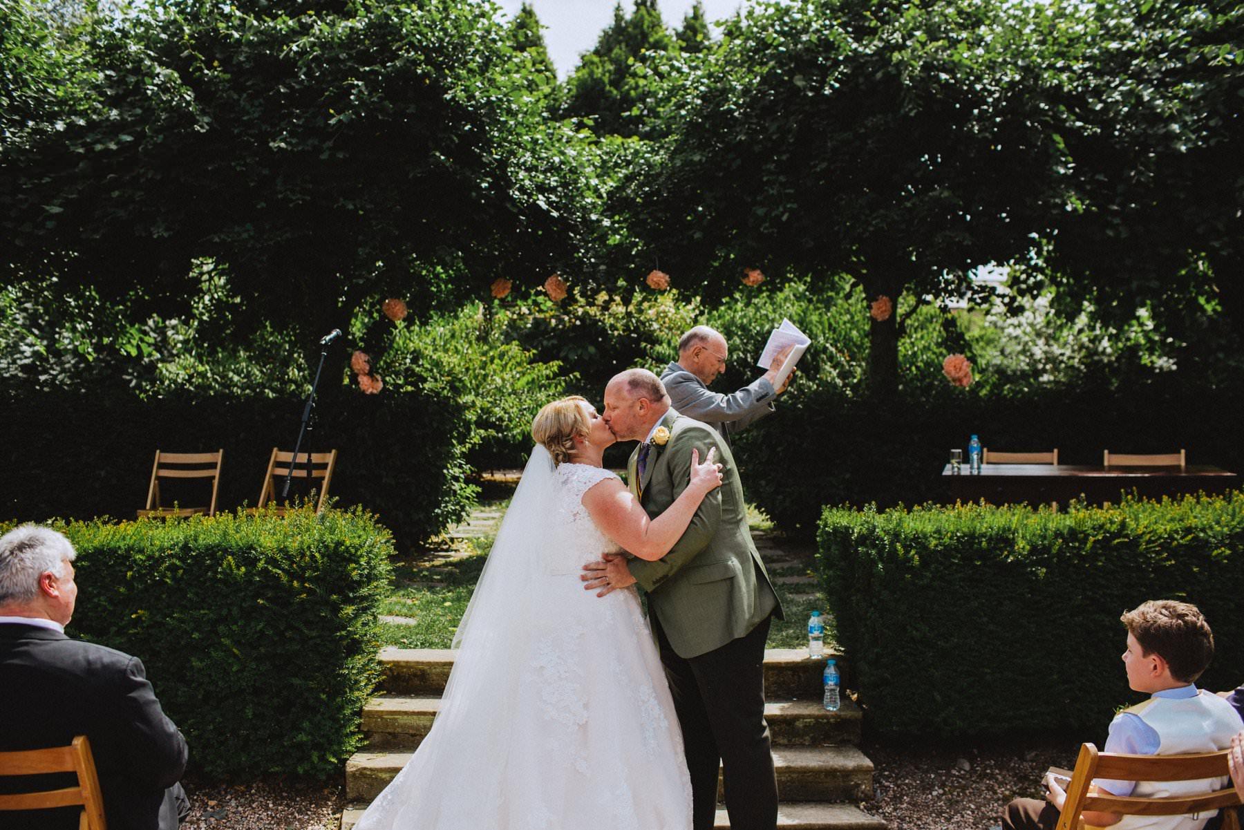 first kiss during outdoor wedding ceremony at larch fields sunken garden