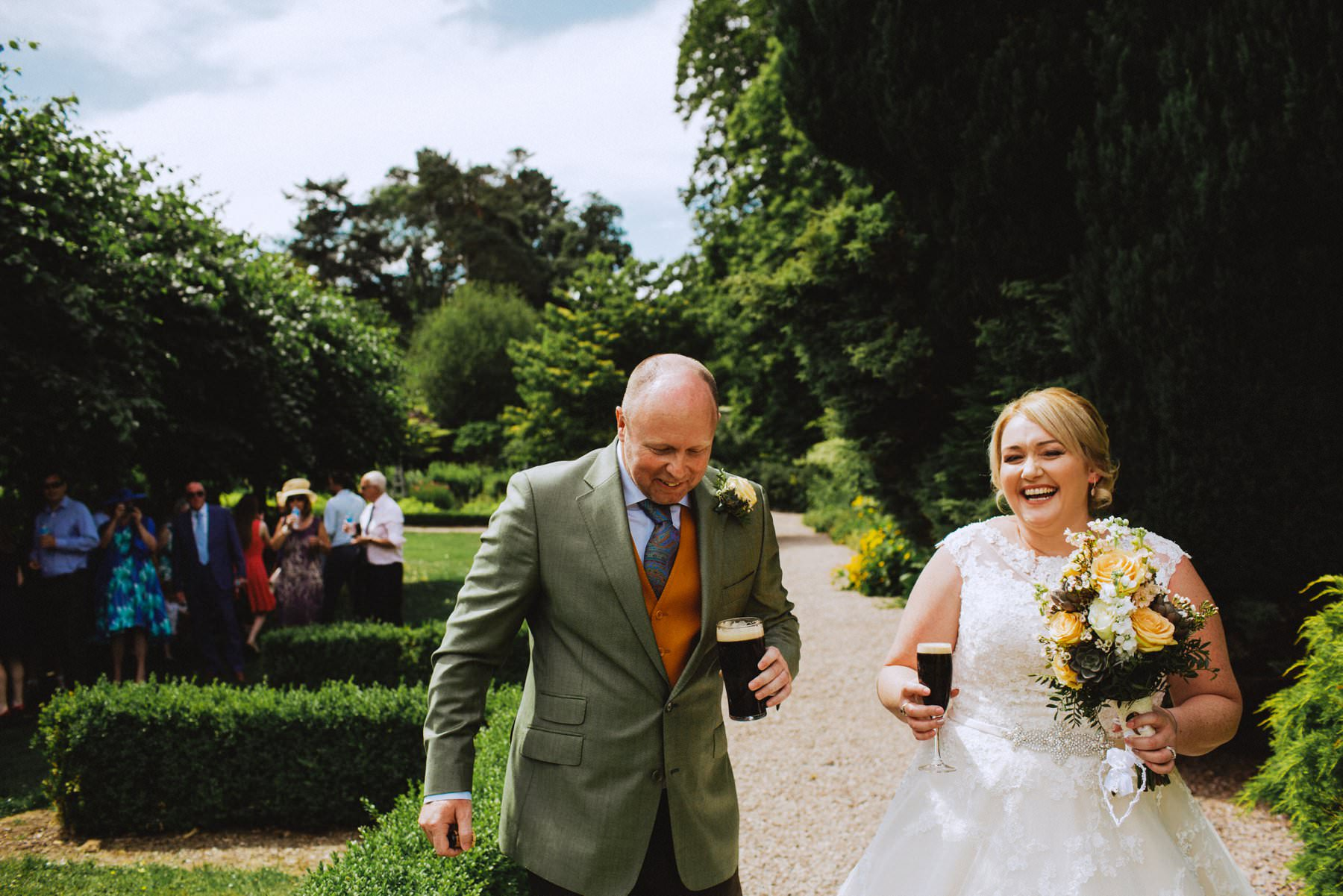 bald groom and plus size bride enjoy a guiness after their outdoor wedding ceremony at larchfield estate northern ireland