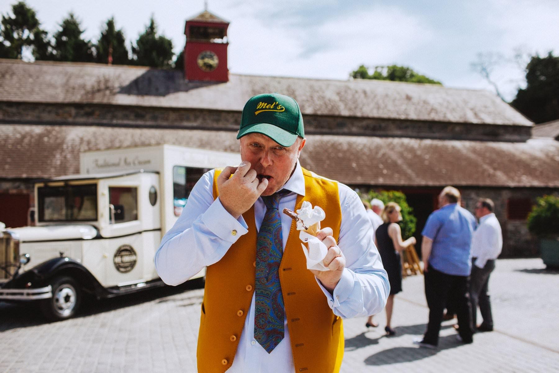 groom in green baseball cap celebrates with soft serve ice cream