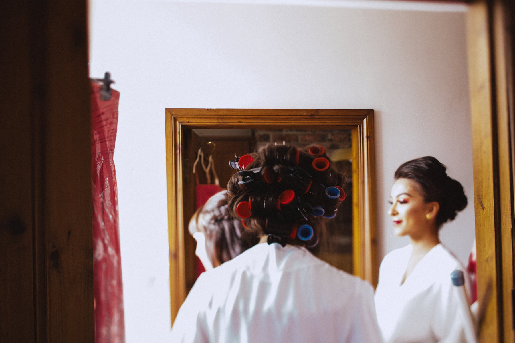 bridesmaids walk through the cottages of larchfield with rollers in their hair