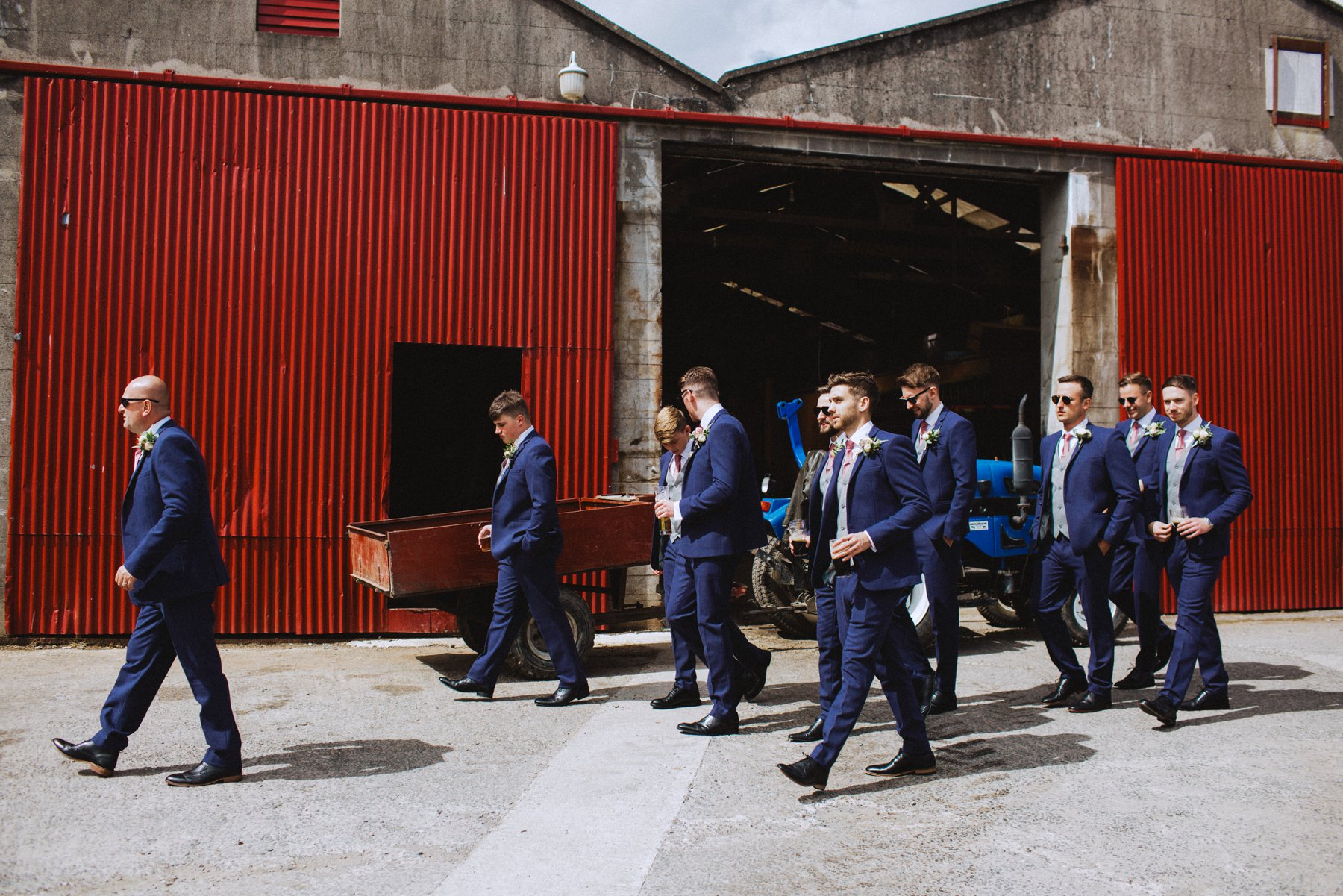 a groom and his 10 groomsmen walk to the out door ceremony at larchfield estate